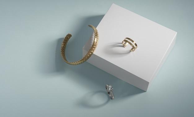 Braccialetto d'oro e anelli su scatola bianca su sfondo blu con copia spazio
