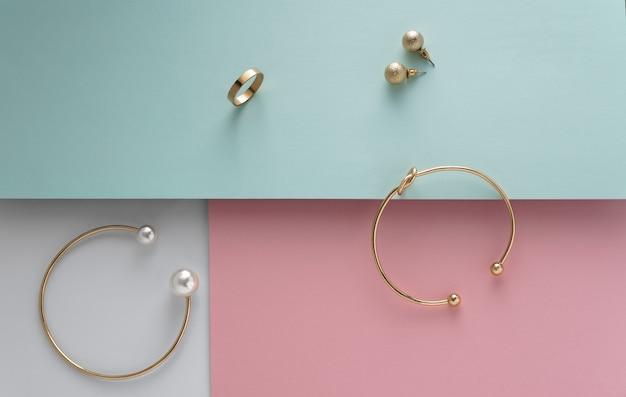 Bracciali e orecchini dorati su sfondo rosa e blu