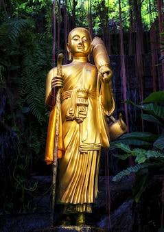 Statua dorata di buddha e piccola cascata artificiale al supporto dorato a wat saket a bangkok, tailandia.