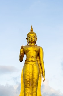Una statua dorata del buddha con il cielo sulla cima della montagna al parco pubblico del comune di hat yai, provincia di songkhla, tailandia