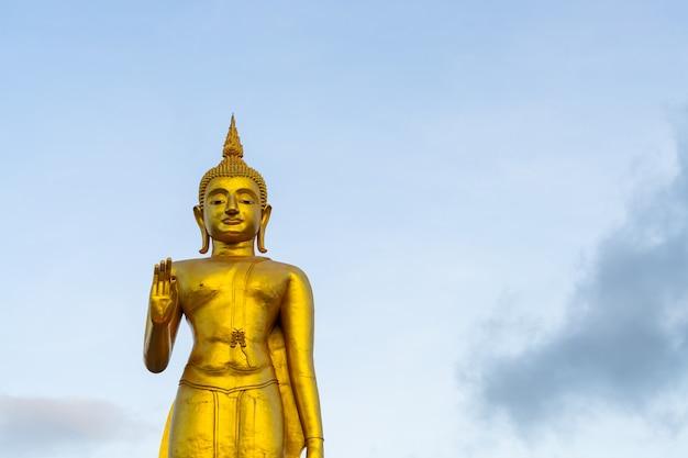 Una statua dorata del buddha con il cielo sulla cima della montagna al parco pubblico del comune di hat yai, provincia di songkhla, thailandia