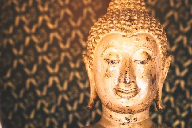 Statua dorata del buddha con luce solare usata per amuleti della religione buddista.