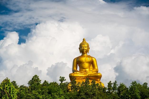 Buddha d'oro e nuvole bianche. statua del buddha con grandi nuvole con copia spazio.