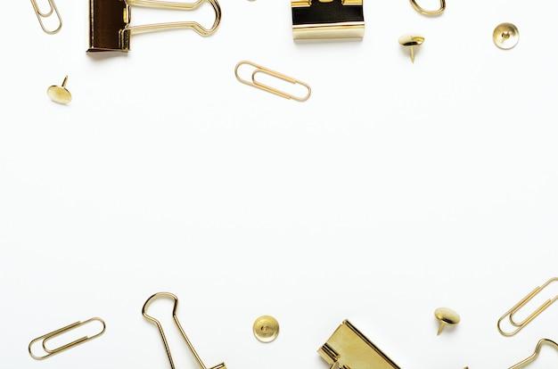 Bottoni dorati, graffette e clip di cancelleria su uno sfondo bianco. cornice di cancelleria per ufficio. copia spazio, vista dall'alto, disteso.