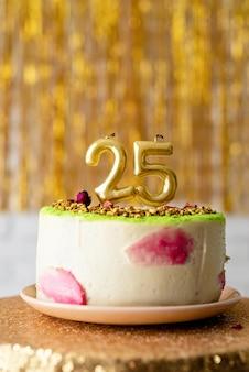 Candele dorate 25 sulla torta di compleanno su sfondo glitter dorato