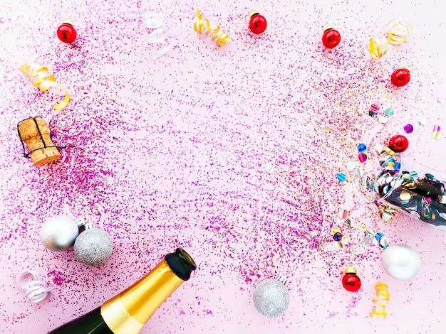 Bottiglia di champagne dorata, paillettes e un bicchiere di coriandoli