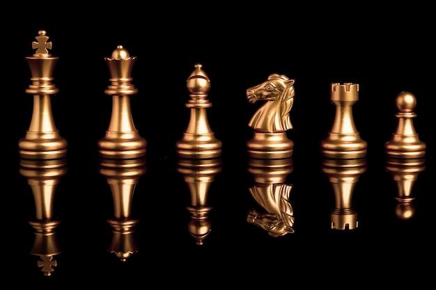 Gli scacchi dorati includono la nave e il pedone del cavallo della regina del re su fondo nero con la riflessione.