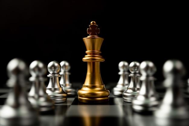 Golden chess king in piedi per essere in giro di altri scacchi, concetto di un leader