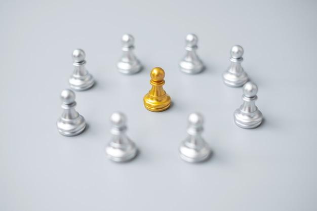 Pezzi di pedina degli scacchi d'oro o uomo d'affari leader leader con cerchio di uomini d'argento. concetto di leadership, affari, squadra e lavoro di squadra