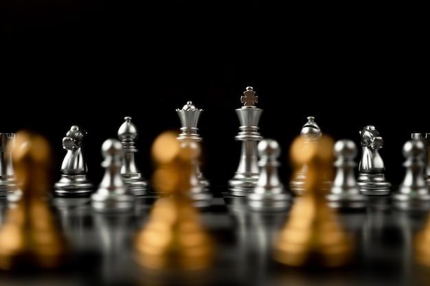 Pedone di scacchi d'oro in piedi di fronte ad altri scacchi