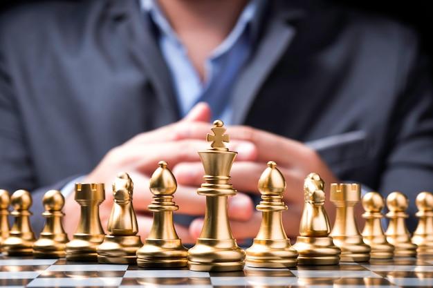 Pezzi degli scacchi dorati sulla scacchiera e davanti all'uomo d'affari.