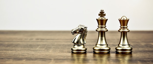 Squadra di scacchi dorata sulla scacchiera, concetto del piano strategico di affari.