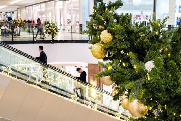Palle e ghirlanda dorate di natale su un albero di abete decorato nel centro commerciale.