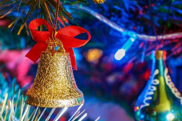 Campana dorata di natale con il nastro rosso contro la ghirlanda colorata luminosa sul ramo del primo piano decorativo dell'abete