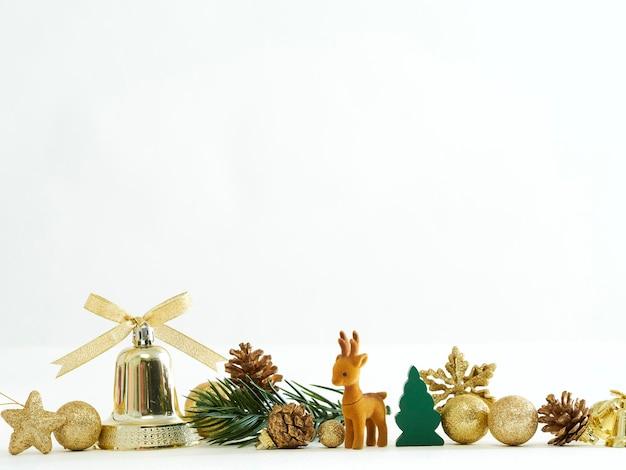 Decorazione dorata di natale con renne, palline, stelle e ramo di un albero di abete su priorità bassa bianca
