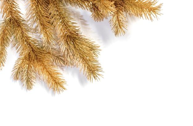 Rami di abete di natale d'oro su sfondo bianco isolato