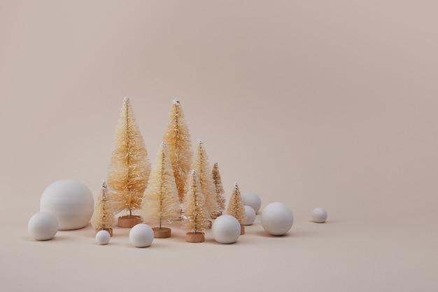 Alberi di natale dorati con palla di neve su sfondo biege.