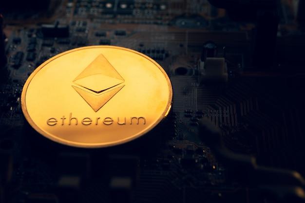 Una moneta d'oro con il simbolo ethereum su una scheda madre.