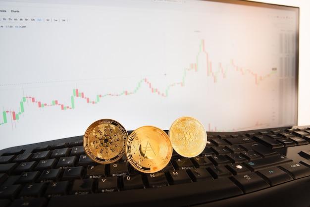 Monete d'oro di criptovalute ada, moneta cardano, controllo del prezzo su un monitor con grafici.