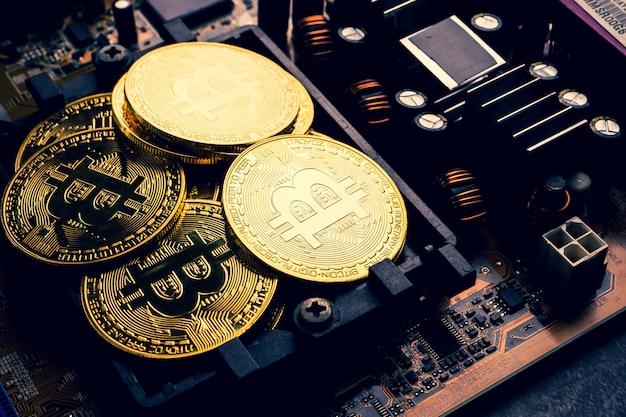 Monete d'oro con il simbolo bitcoin su una scheda madre.