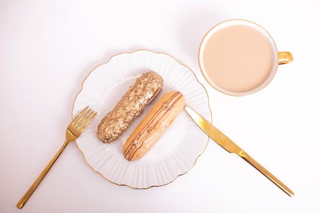 Eclair color oro su piatto con coltello e forchetta dorati e una tazza di caffè su sfondo bianco