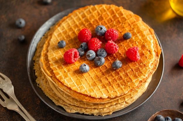 Cialde rotonde croccanti dorate servite su piatto con frutti di bosco. avvicinamento.