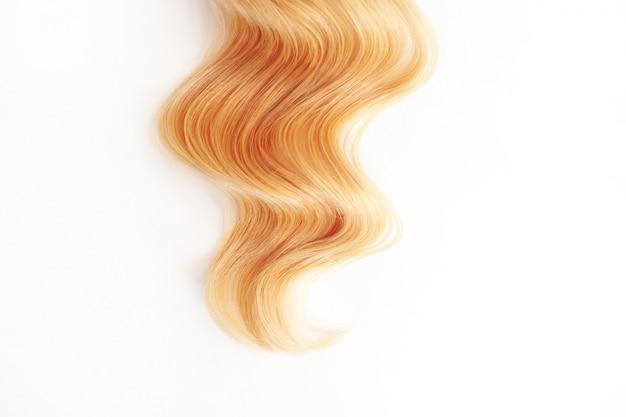 Capelli dorati dei riccioli isolati. ciocca di capelli biondi o rossi, cura dei capelli