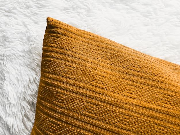 Cuscino d'oro cuscino da tiro su soffice coperta scozzese bianca come sfondo piatto camera da letto vista dall'alto e arredamento per la casa flatlay