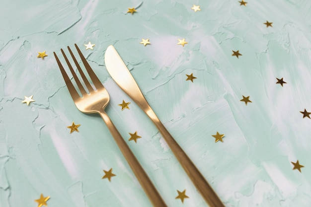 Posate d'oro, forchetta e coltello e coriandoli di stelle di lamina d'oro su verde