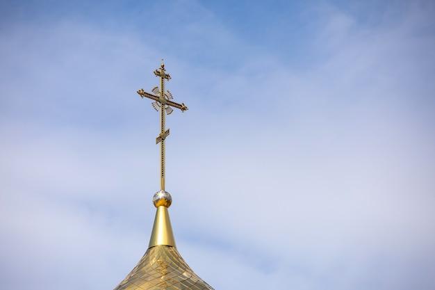La cupola dorata e la croce della chiesa ortodossa contro il cielo azzurro e le nuvole.