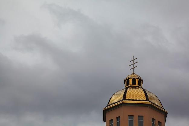 Chiesa ortodossa delle cupole dorate con la croce contro il cielo blu
