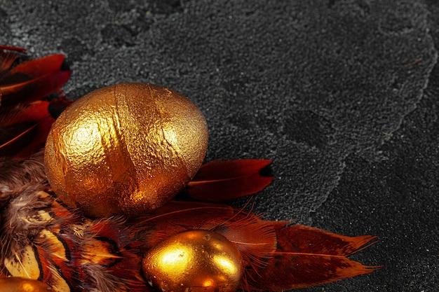 Le uova di pasqua dorate sulle piume di uccello rosse si chiudono su
