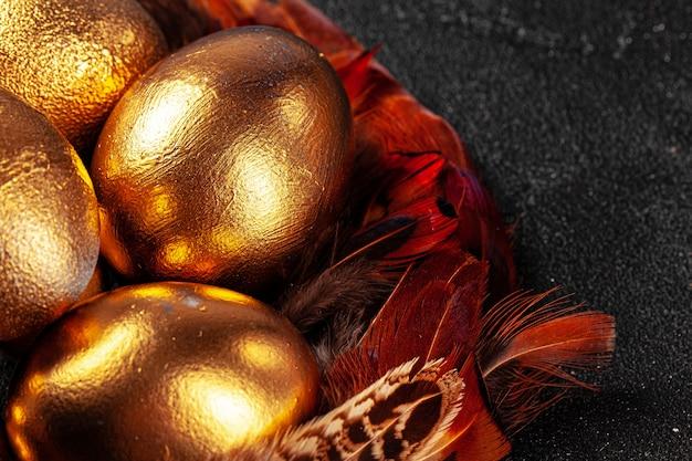 Uova di pasqua dorate sulle piume di uccello rosse