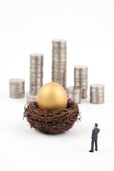 Uovo e uomo dorati di affari su fondo bianco
