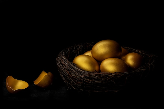 Uovo dorato e guscio d'uovo nel nido isolato su sfondo nero