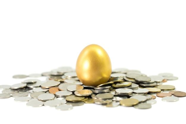 Uovo d'oro con monete su sfondo bianco