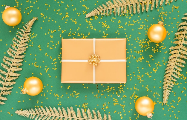 Foglie di felce d'oro e scatole regalo con palline di natale su sfondo verde con stelle d'oro glitter