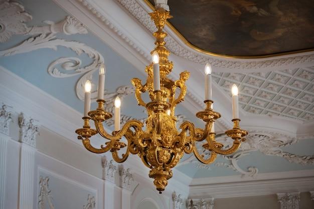 Lampadario figurato dorato con candele elettriche sul soffitto con stucchi e dipinti nel palazzo