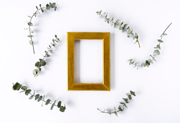 Una cornice dorata per copia spazio e foglie verdi di eucalipto intorno su uno sfondo bianco. copia spazio