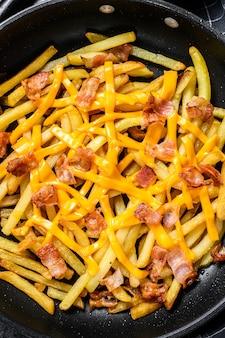 Patate fritte dorate fritte con formaggio cheddar e pancetta in padella. vista dall'alto.