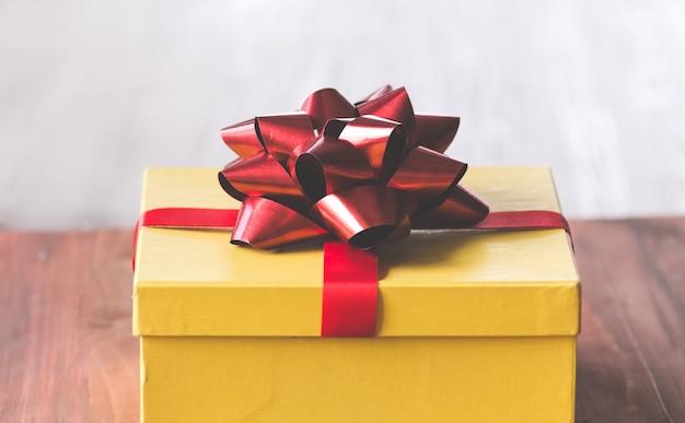 Contenitore di regalo dorato e nastro rosso sulla priorità bassa di colore