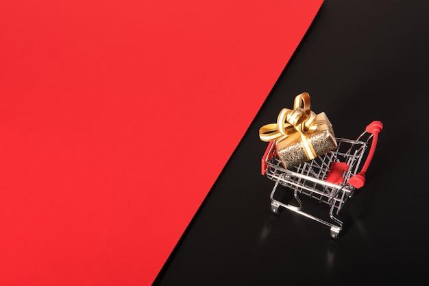 Confezione regalo dorata e carrello della spesa su sfondo rosso nero. vendita del venerdì nero.