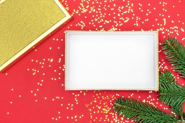 Regalo d'oro su sfondo rosso, vista dall'alto di scatola regalo.