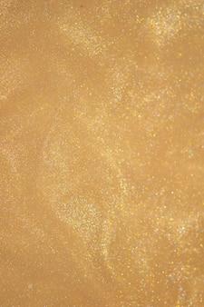 Polvere di scintillio dorato su sfondo scuro.