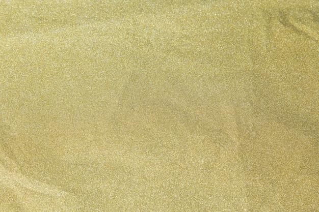 La carta brillante di scintillio dorato è sgualcita per fondo di natale, concetto di celebrazione.