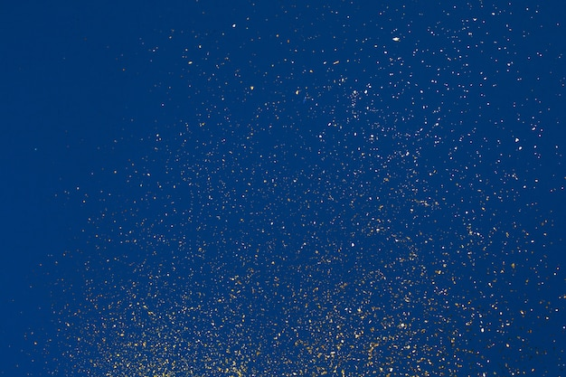 Struttura astratta granulosa dorata su sfondo blu. concetto di colore del 2020. tendenza principale dell'anno. natale