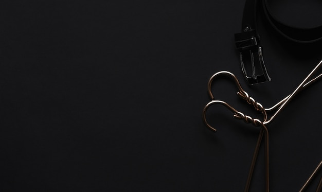 Gancio dorato e cintura nera sul tavolo nero. accessori uomo e attrezzatura per la bellezza.