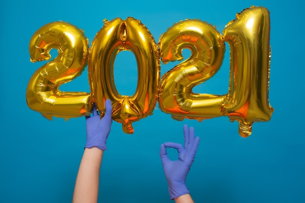 Palloncini di elio dorato con numeri 2021 vicino all'albero di natale isolato su priorità bassa blu. coronavirus.