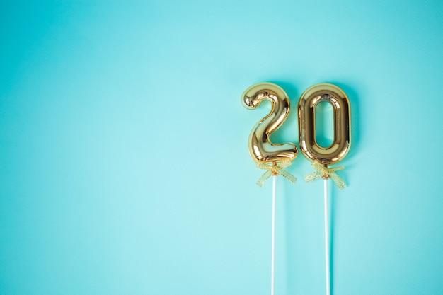 Palloncini gonfiati dorati con 20 numeri festivi su sfondo blu.