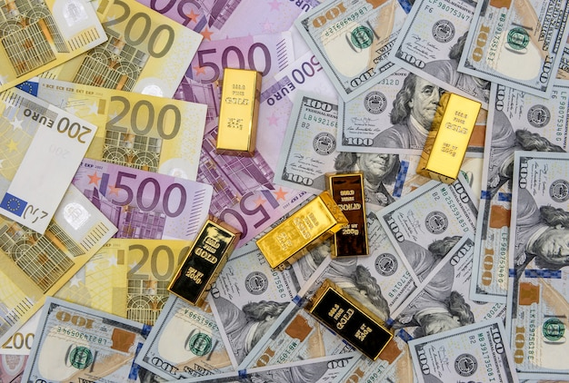 Lingotto d'oro su dollari americani e banconote in euro